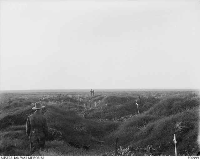 An unidentified soldier views the Australian graves along the old OG1 (Old German) line on the battlefield of Pozieres. All these graves have been marked and recorded by the Graves Registration Section.
